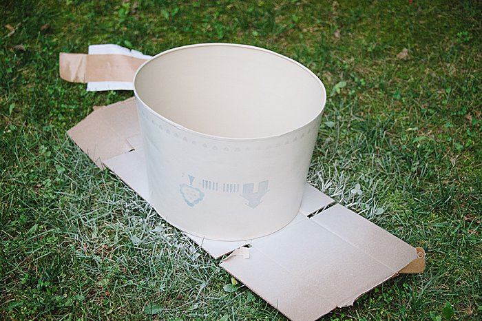 Spray paint an old lamp shade with primer to cover up any patterns, designs or stencils before wrapping in burlap