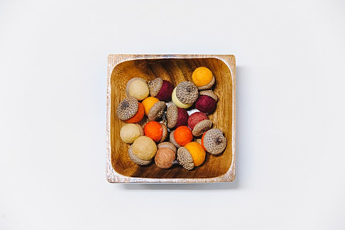 felt acorns can be displayed in a wooden bowl or other decorative dish