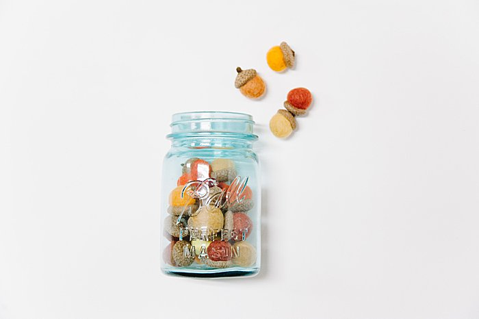 a blue mason jar is the perfect place to display felt ball acorns