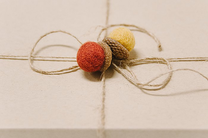 hot glue felt ball acorns onto twine when you wrap a gift