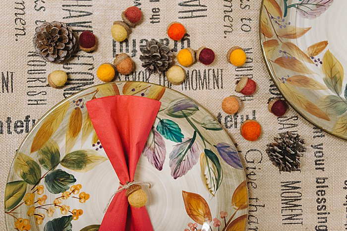fall or thanksgiving place setting can use felt ball acorns as napkin holders and scatter felt acorns and pine cones on the table