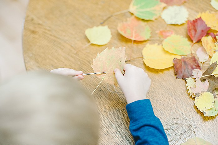 threading leaves onto twine is a fine motor activity for kids