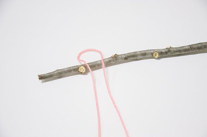 loop yarn around stick to create wall hanging from yarn