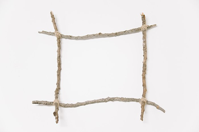 hot glue corners and tie twine around sticks to secure in the corners