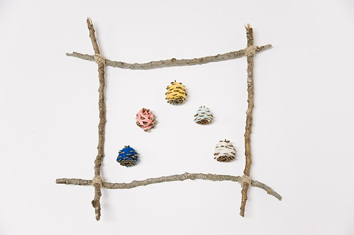 hang yarn wrapped pine cones from a picture frame made from sticks to make wall art