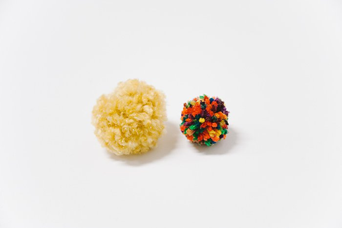 size comparison between yarn pom poms made with different kinds of yarn