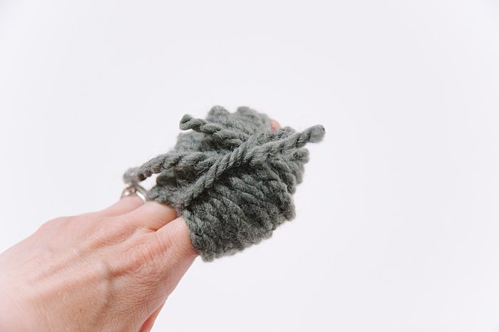 making a pom pom with thick chunky gray yarn