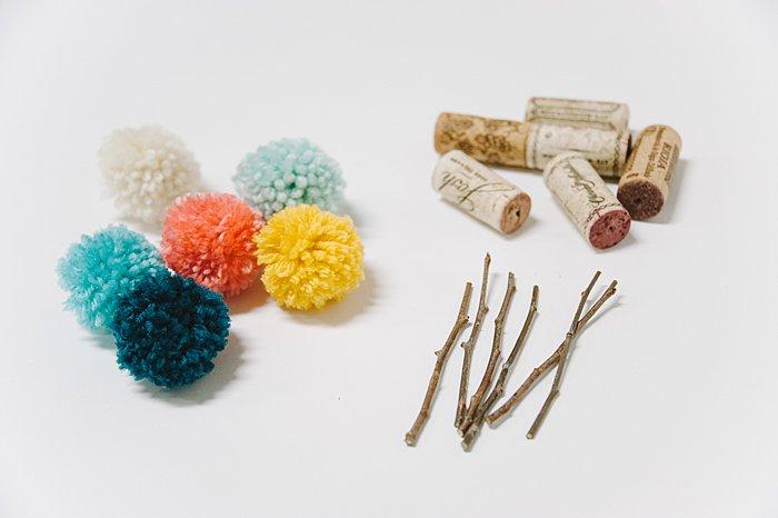 yarn pom poms, sticks and wine corks