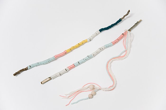 add string and beads to make a diy nature wand from yarn wrapped sticks