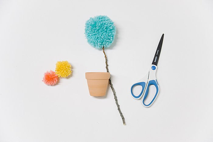 making a potted flower in a mini clay pot with a big pom pom made of yarn