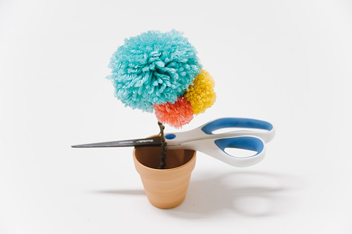 hot glue pom pom flower into clay pot and let glue dry completely