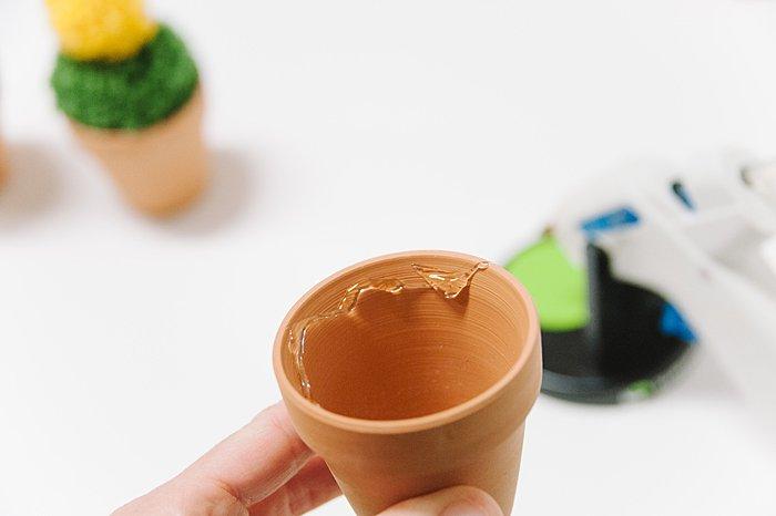hot glue yarn pom pom inside clay pot to make a cactus