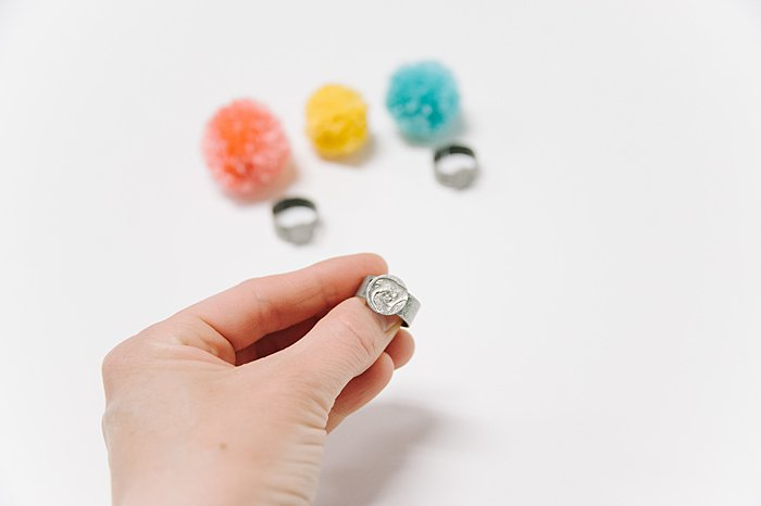 hot glue pompom onto ring blank to make a ring