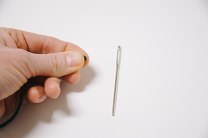 hold the thread right at the tip, between your thumb and pointer finger.
