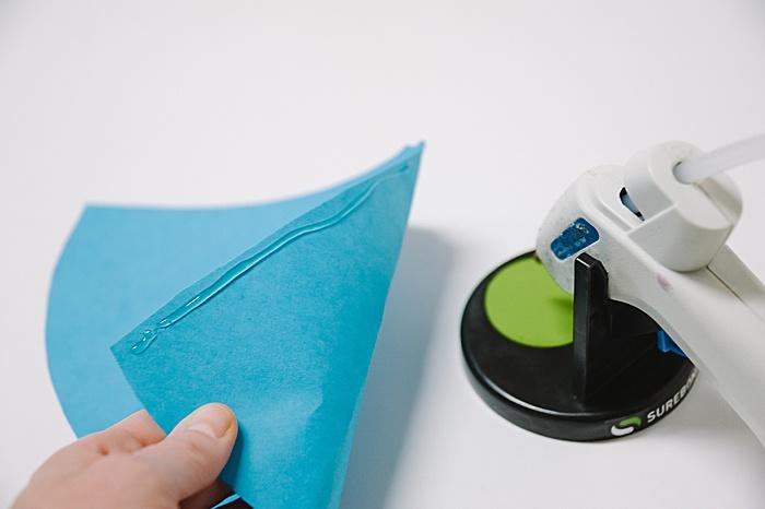 use hot glue gun and hot glue sticks to secure paper cone shape into a cone