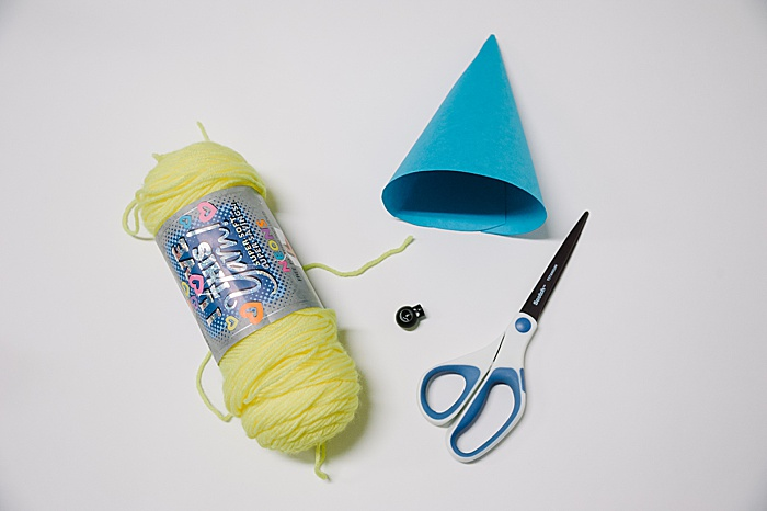 turn a paper cone into a party hat with scissors, yarn, a fastener, and a hole punch