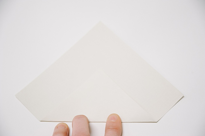 fold the bottom corner of the square paper up to a little over half way