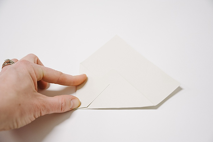 fold the left corner of the paper into the middle and press edge flat