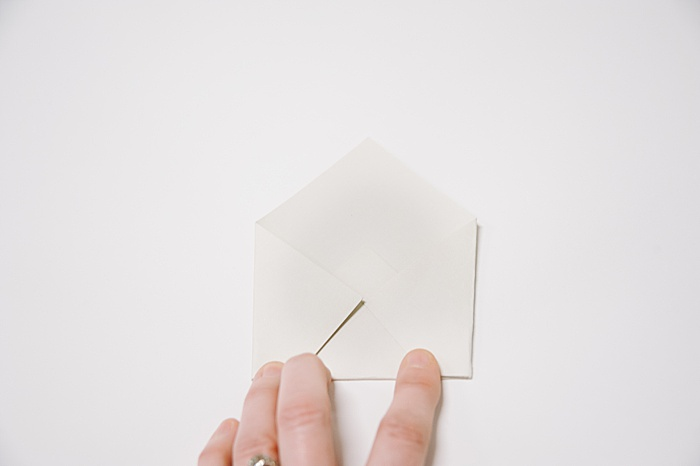 fold the right corner of the paper into the middle and press the edge flat
