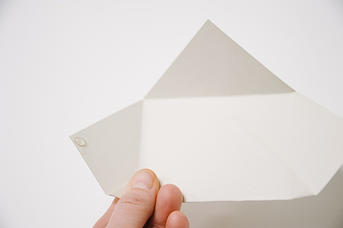 put a dab of hot glue on the left flap of the paper envelope to secure