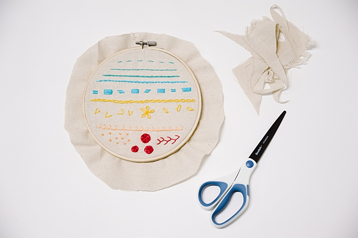 """Trim excess fabric to 1-2"""" around the perimeter of the hoop."""