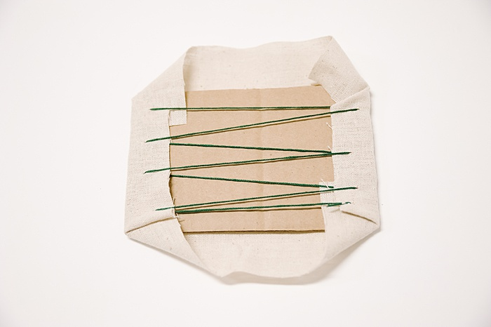 use a lacing stitch to sew up the back of the fabric around the cardboard