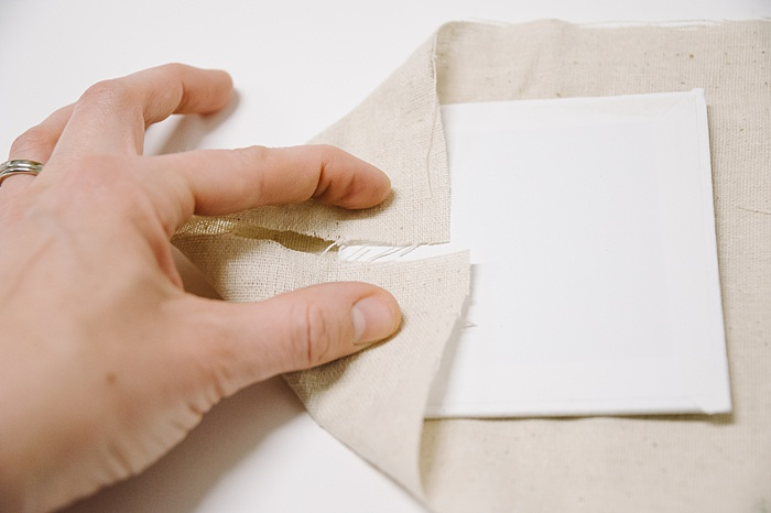 fold two corners of fabric toward the middle, to wrap a canvas in embroidery