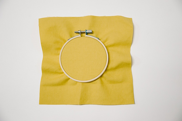 how to use an embroidery hoop by pushing outer hoop down over inner hoop and fabric to pull it tight