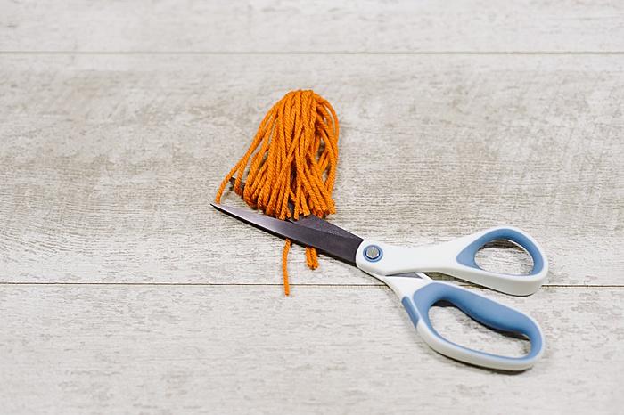 trim the loops at the bottom of the diy yarn tassel