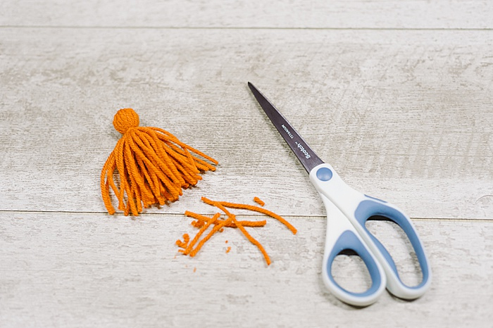 Trim the bottom of the diy tassel to clean the yarn up