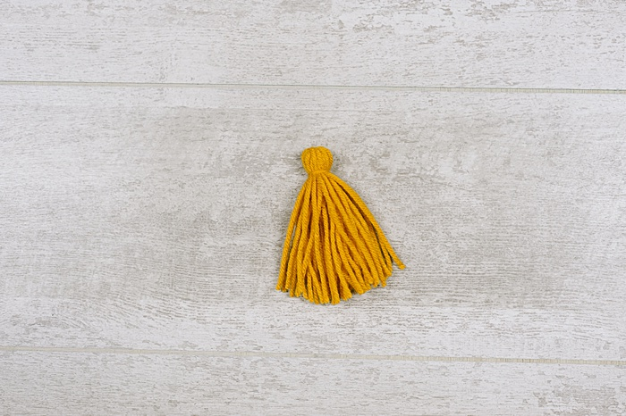 tutorial showing how to make tassels out of yarn with cardboard