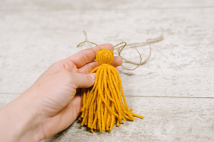 tie a knot in the twine at the top of the tassel