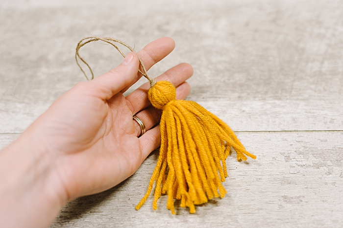 knot the twine at the top of the yarn tassel