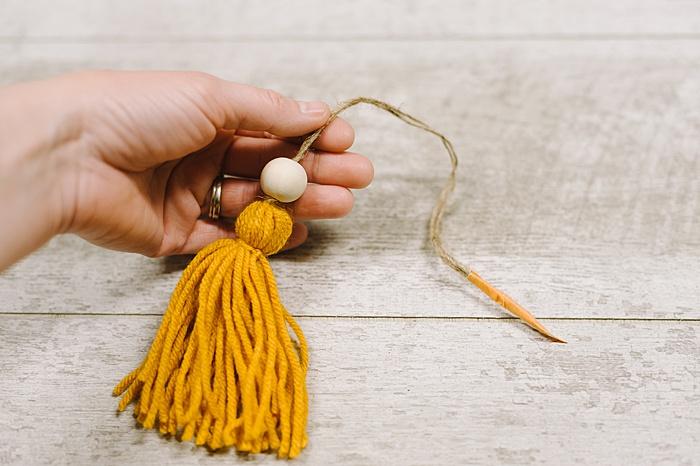 add beads to wood bead tassel ornament