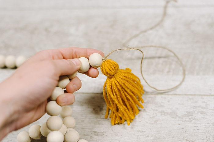 knot the string to attach the tassel to the garland