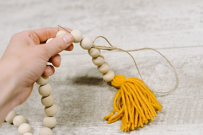 thread needle and twine up through the beads to hide
