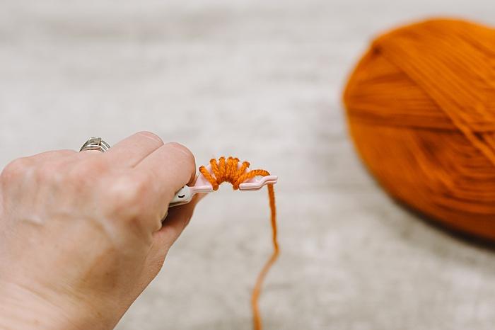 wrap yarn around pom pom maker