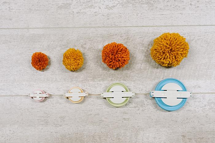 different sizes of pom poms made with pom pom makers